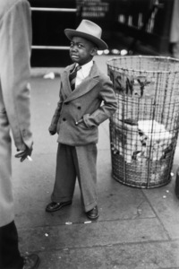 A full-length image of a young boy, wearing a hat, suit and tie, crying while standing next to a trash bin on the street, New York City1948© 1978 Ruth Orkin - Image 24388_0029