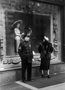 A police officer stands with his hand in his pants pocket while a middle-aged woman looks at a mannequin in the window of Saks Fifth Avenue department store, New York City1948© 1978 Ruth Orkin - Image 24388_0034
