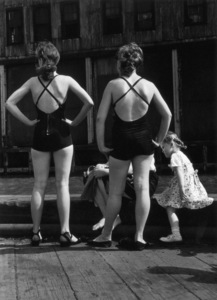 A full-length image of two women wearing swimsuits, viewed from behind, standing with their hands on their hips in front of another woman and child, who are seated, Gansevoort Pier, New York City1948© 1978 Ruth Orkin - Image 24388_0038