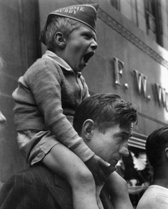 A boy yawning on his father