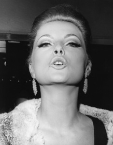 """Virna Lisi obliges with a glamour pose for photographers upon her arrival at the El Morocco night club in New York where she was attending an after-premiere party following the opening of her new movie """"How to Murder Your Wife"""" / 1965 - Image 2603_0016"""