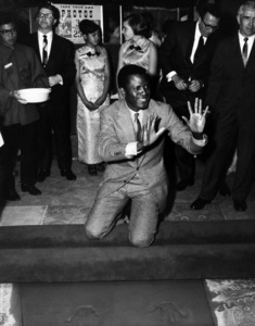 Sidney Poitier signing his name in cement at Grauman