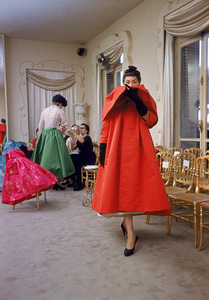 """""""Fashion""""Model wearing Balenciaga orange coat as I. Magnin buyers inspect a dinner outfit in the background / Paris, France 1954 © 2002 Mark Shaw - Image 3956_0913"""