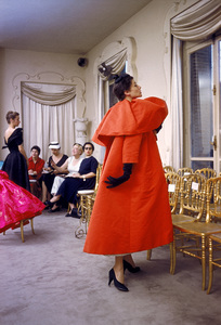 """""""Fashion""""Model wearing Balenciaga orange coat as I. Magnin buyers inspect a dinner outfit in the background / Paris, France 1954 © 2002 Mark Shaw - Image 3956_0914"""