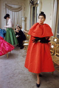 """""""Fashion""""Model wearing Balenciaga orange coat as I. Magnin buyers inspect a dinner outfit in the background / Paris, France 1954 © 2005 Mark Shaw - Image 3956_0923"""