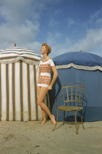 """Photographed by Mark Shaw for the Jan. 14, 1957 issue of Life, this model poses in a Givenchy designed tunic with a Moorish pattern made of elasticized cotton. The Life article, """"French Flavor for U.S. Beaches"""" featured fashions photographed on the beach at Trouville and the harbor of Honfleur, France © 2010 Mark Shaw - Image 3956_1047"""
