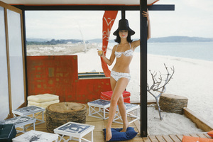 Model Christine Mayer wears a white organdy bikini in a Japanese style beach cabana that was located at St. Tropez