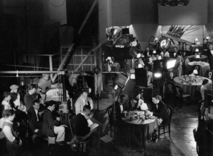 """Stamboul Quest"" Myrna Loy, George Brent, director Sam Wood (sitting in front of the camera), cinematographer James Wong Howe (behind the camera in white trousers) 1934 MGM Photo by Ted Allan"