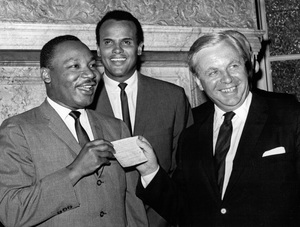 Dr. Martin Luther King Jr. happily accepts a check for $100,000 from Tore Tallroth, Sweden