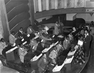 """Billy Eckstine and his band performing at The Aragon Ballroom in Pittsburgh, Pennsylvania (FRONT ROW: Billy Eckstine, Sarah Vaughan SECOND ROW: Eli """"Lucky"""" Thompson, Sonny Stitt, Charlie Parker, Leo Parker, Gene Ammons THIRD ROW: Benny Green, Gail Brockman, Shorty McConnell, Tommy Potter FOURTH ROW: Unknown, Theodore """"Fats"""" Navarro, Howard McGhee, Dizzy Gillespie, Art Blakey)1944Photo by Charles """"Tweenie"""" Harris** I.V.M. - Image 4867_0025"""