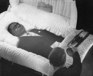 Artie Seifert, a commercial artist, places a battered trumpet on the coffin of Louis Armstrong at New York