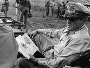 """""""MacArthur""""Gregory Peck holding cartoon of President Harry Truman cutting off oxygen to MacArthur1977 Universal Pictures© 1978 Larry Barbier - Image 6783_0014"""