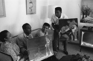 Cassius Clay in the living room of his Louisville, Kentucky home with his mother, Odessa, father, Cassius Sr., and brother, Rudy, looking at Cassius Sr.