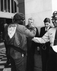 Black Panther member with state police Lt. Ernest Holloway at state capitol building in Sacramento, CA1967 - Image 7950_0001