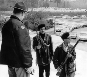 Two rifle-carrying Black Panthers, part of a group of six who marched up the steps of the state capitol building with loaded weapons, are confronted by state patrol Capt. R. J. Ranney / Olympia, WA / 1969 - Image 7950_0003