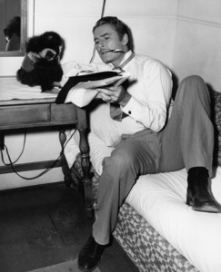 """Errol Flynn with his trained gibbon, Chico, during the making of """"Silver River""""1948 Warner BrothersPhoto by Lloyd MacLean - Image 9227_0002"""