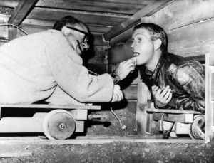 """""""The Great Escape""""Make up man Emile Lavigne making Steve McQueen dirtier for the next take1963U/A - Image 9429_0013"""