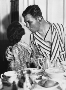 """Boxers / Boxing""Mrs. James Braddock gives the final congratulations in the form of a big kiss to husband Jimmy Braddock, at their suite in the Mayflower Hotel, New York City, following his electrifying defeat of Max Baer, an eight-to-one favorite over him at the start of their championship bout last night / June 15, 1935 - Image 9919_0039"