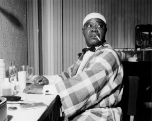 Louis Armstrong relaxing backstage, Finsbury Park Astoria, London 1962Photo by Brian Foskett © National Jazz Archive - Image FOS_0003